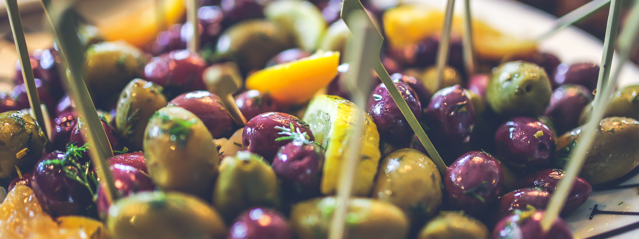 Purple and green olives seasoned with fresh herbs and covered in oil. Olive oil is one of the products we offer in oils and fats of Nutritional Food Ingredients Solutions.